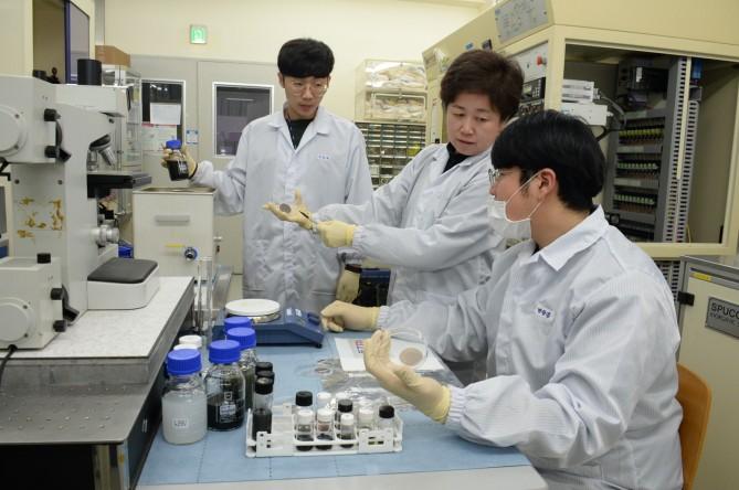 ETRI 연구진이 물과 나트륨 이온을 활용하여 제조된, 2차원 나노재료가 담겨 있는 수용액을 살펴보고 있다.